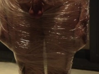Male slave bound in cling wrap gets riding crop CBT by two gorgeous Femdoms