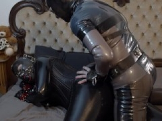 Latex Couple play in full rubber. Miss Maskerade in slave bound and gag by Master